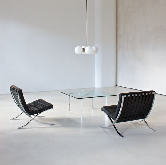 Two Barcelona Chairs in a room with a Barcelona Table